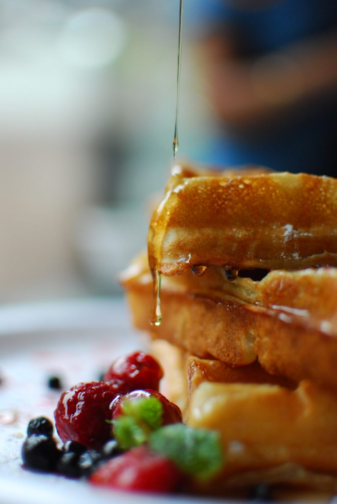 Syrup being poured onto a stack of waffles
